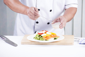 Chef putting salad dressing