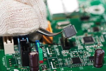 Micro chip held with tweezers over motherboard