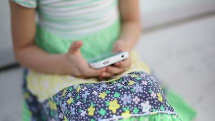 Beautiful child little girl enjoys smartphone close up