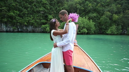 pretty brunette girl with her boyfriend on a longtail boat