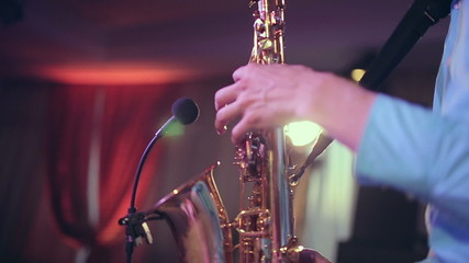 Saxophone player performs on stage with professional light