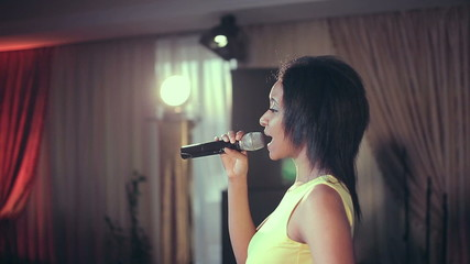 Black woman singing a song on stage at the microphone.