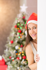 Girl with Santa's hat peeking behind the door