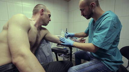 Tattoo artist working. Man draws on his arm woman's face.