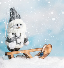 Happy snowman on a sled
