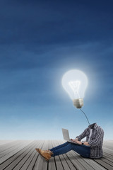 Casual student with lamp head using laptop