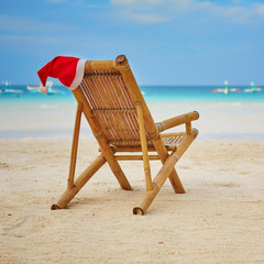 Santa hat on chaise longue on white sand beach