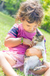 outdoor portrait of young child girl with small kitten, girl pla