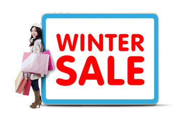 Female shopaholic lean on winter sale text