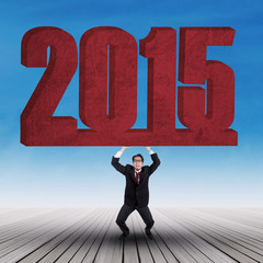 Strong businessman lifting number 2015