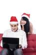 Woman in santa hat see her boyfriend with laptop