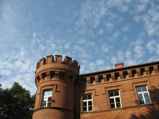 Строгие формы дворцовой башни на фоне голубого неба