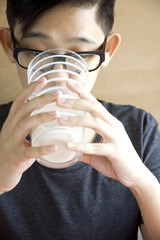 young asian drinking milk