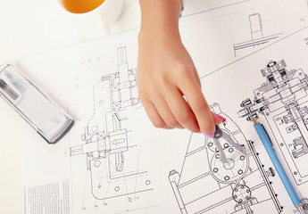 Female architect working with blueprints at office desk
