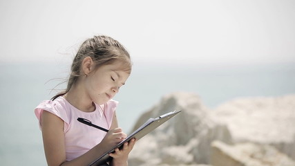 A child sits on a stone near the Adriatic Sea and draws
