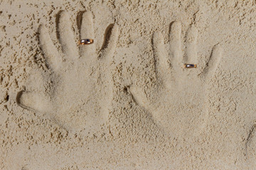 two hand prints with wedding rings on tropical sand beach, outdo