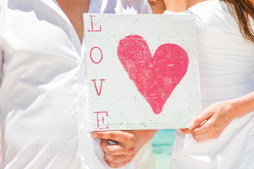 bride and groom holding sign with love word on tropical sea back