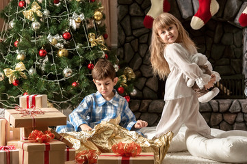 Children under the Christmas tree dismantled gifts