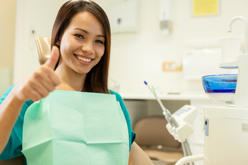 smiling asian woman sitting at the dentist and smiles towards th