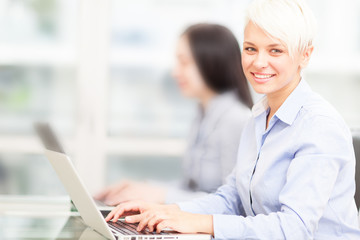 smiling employee portrait with blurred people background