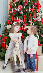 Small boy and the girl play near a beautiful Christmas fir-tree
