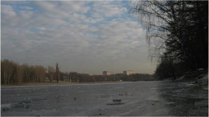 зимний пруд лднем с облаками