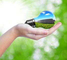 Hand holding solar panels in light bulb. Green energy concept.