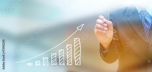 Leinwandbild Motiv businessman hand writing a business graph on a touch screen inte