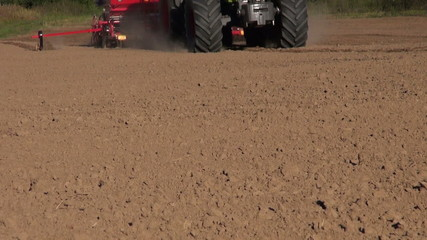 modern new agriculture tractor seeding crop grain on farm field