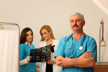 Mature male doctor with two female nurses