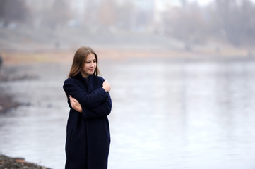 the girl in a blue coat walks along the river