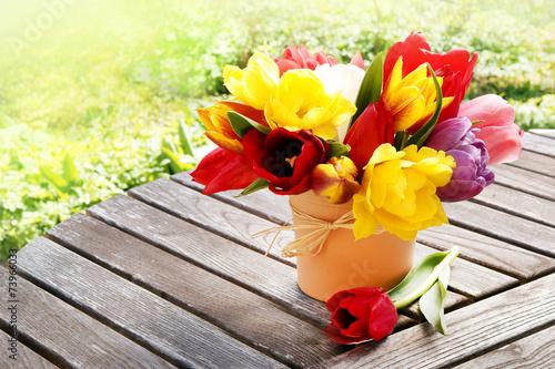 canvas print picture farbenfrohe Tulpen auf Gartentisch