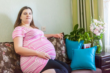 Pregnat woman resting at home with beautiful flowers