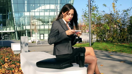 Businesswoman browsing internet on smartphone outside