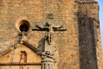 cruz de piedra frente a la iglesia romanica de pesquera de ebro
