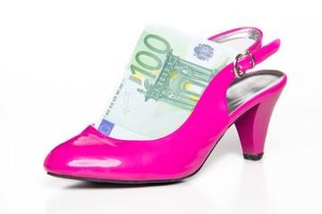 Feminine pink high-heeled shoe and 100 euro