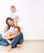 Happy family on  floor near  empty  wall in the apartment