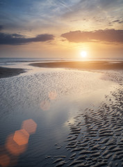 Beautiful vibrant Summer sunset over golden beach landscape with