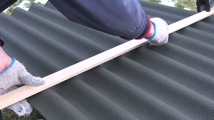 workers measure and marks roof material sheet