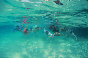 Group of young friends swim diving underwater