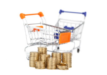 coins in a column on the background shopping carts. focus on coi