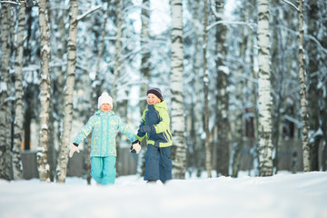 Happy children walking in winter day.