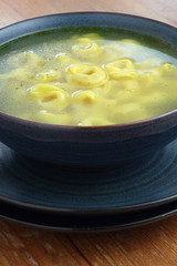 Bowl of chicken broth and tortellini on a wooden tabletop.