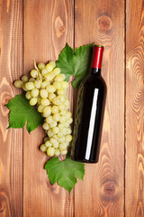Red wine bottle and bunch of white grapes