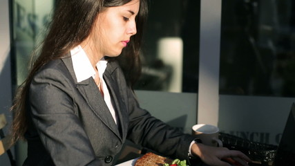 Businesswoman working on laptop outside the cafe and smiling