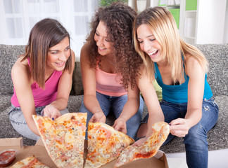 Three cheerful young woman eating pizza at home