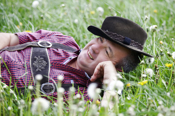 Man with hat lying in the spring meadow