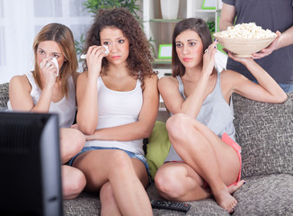 group of young women sitting on couch watching sad movie depress
