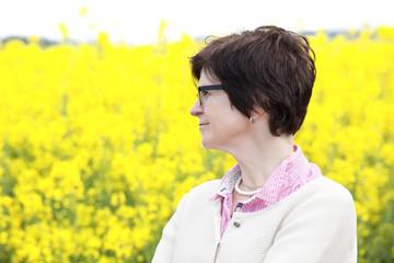 Farmer on flowering canola field