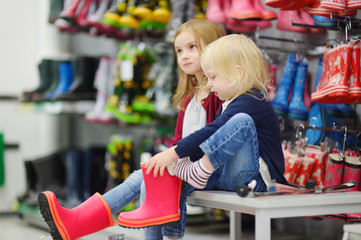 Two sisters choosing and trying on new rain boots
